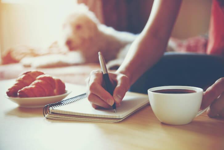 Zdjęcie kobiety piszącej dziennik wdzięczności