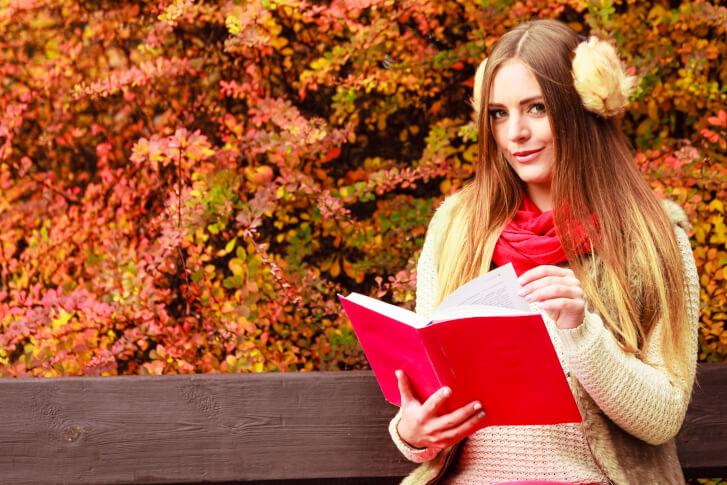 Piękna kobieta czytająca książkę w parku, na tle malowniczej jesieni