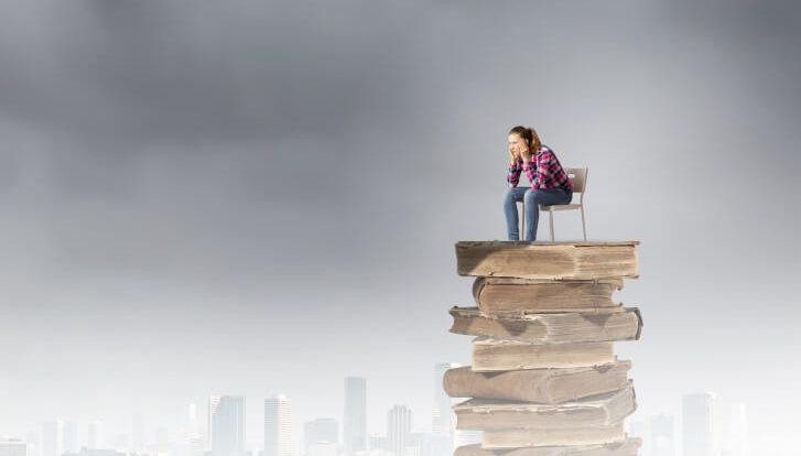 Zmartwiona kobieta siedząca na szczycie sterty zgniłych książek