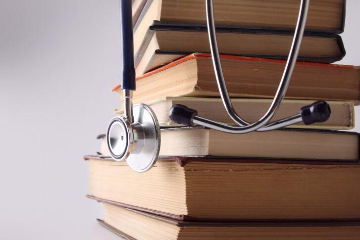 Sterta książek, na których wisi lekarski stetoskop.