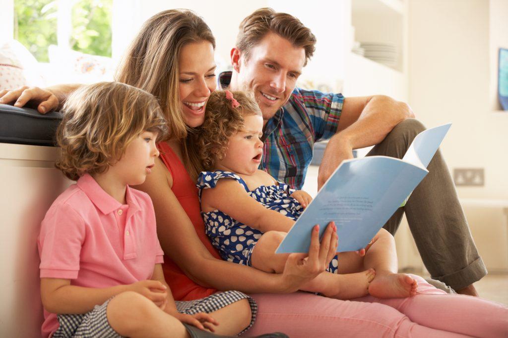 Rodzice czytają książkę dwójce swoich dzieci.