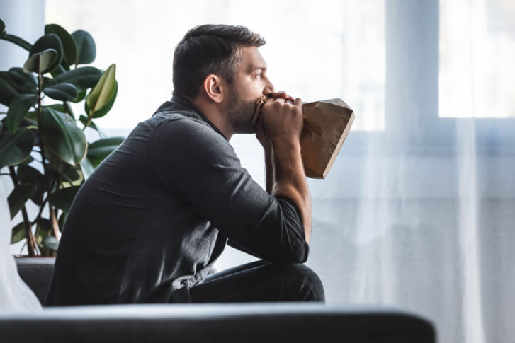Mężczyzna oddychający z torbą przy ustach, aby zmniejszyć hiperwentylację i złagodzić atak paniki