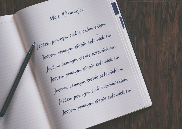 """zeszyt z ręcznie napisanym tekstem """"moje afirmacje"""", oraz wielokrotnie powtórzonym tekstem """"Jestem pewnym siebie człowiekiem""""; długopis."""