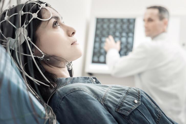 kobieta z elektrodami na głowie przechodzi badanie pod okiem lekarza