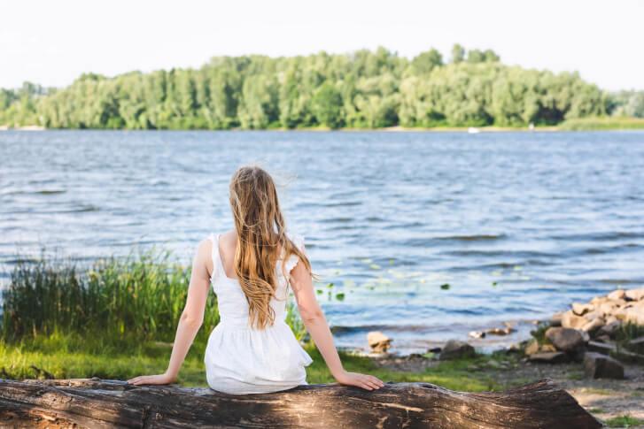 Kobieta siedząca na brzegu rzeki