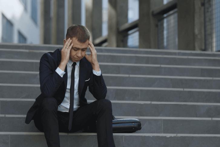 pracownik korporacji siedzi na schodach z głową w dłoniach