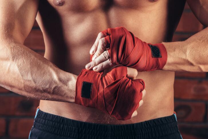 Mężczyzna zawiązuje rękawice bokserskie