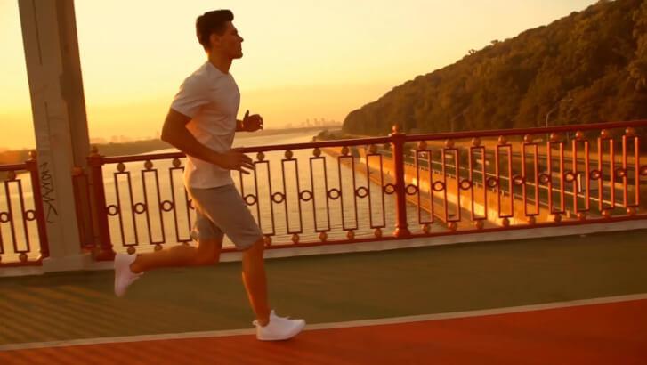 mężczyzna biegnie przez most w czasie wschodu słońca