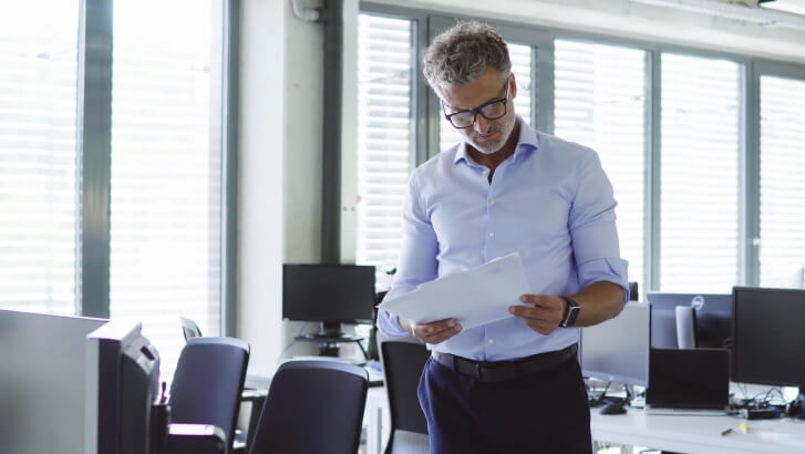 mężczyzna czyta coś z kartki intensywnie myśląc w pustym biurze.
