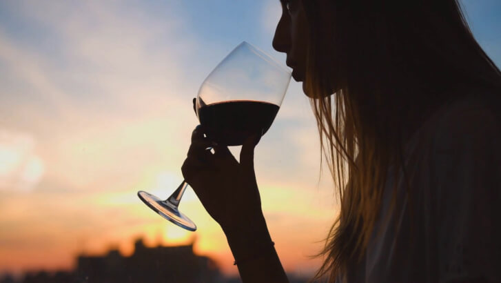 kobieta pije wino na tle zachodzącego słońca