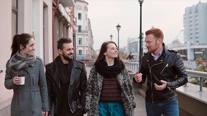 Cztery osoby idące, słuchające jednej z nich z lekką drwiną